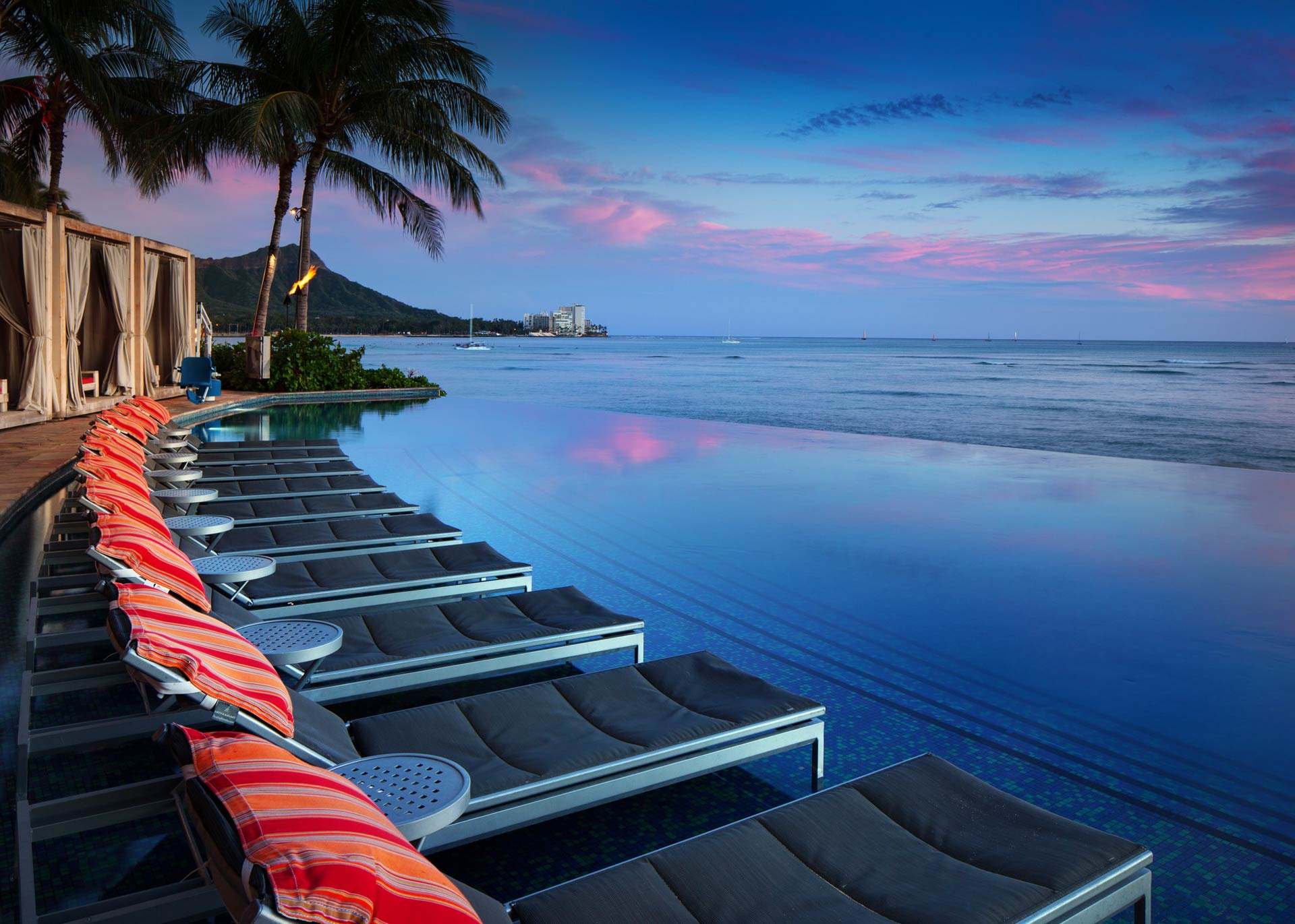 lined black-and-grey chaise lounge chairs overlooking body of water