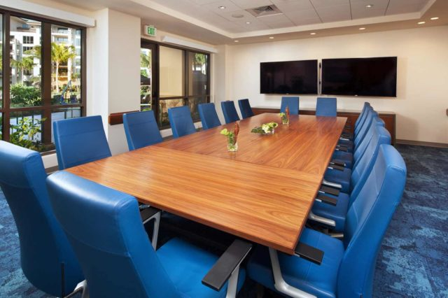 brown wooden conference table surrounded by blue armchairs indoors