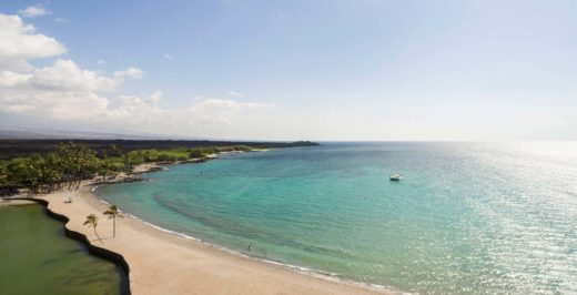 View of the beautiful golden-sand beach and turquoise water of Waikoloa Beach on 'Anaeho'omalu Bay on a sunny day.