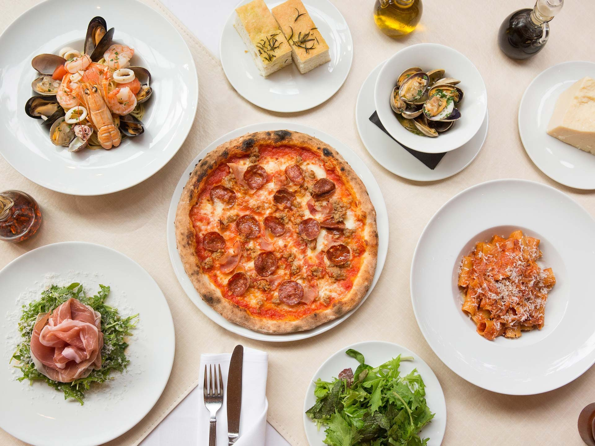 a table set with a number of Italian dishes such as pizza, pasta, salads, and fresh seafood
